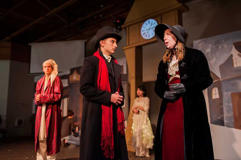 KAREN HAWLEY PHOTOGRAPHY - Jake Byrne, left foreground, plays the young Scrooge talking to his lost love, Belle, played by Jessie Turner, as Brook Mackaness, playing the older Scrooge in nightcap, looks on.
