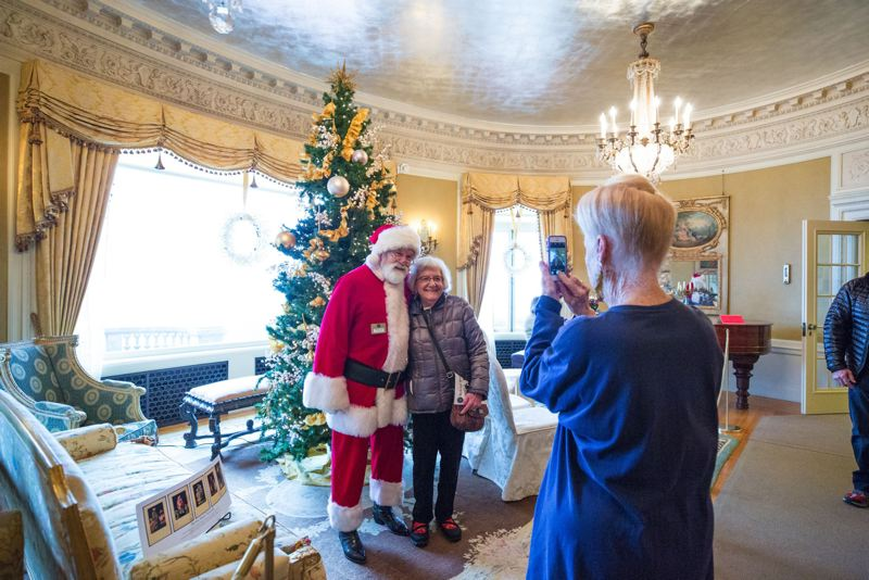 TRIBUNE PHOTO: JONATHAN HOUSE - Santa poses with guests at Pittock Mansion.