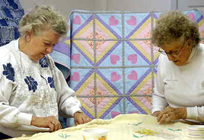 by: MICHELE BERTALOT/CENTRAL OREGONIAN - Virginia Misfeldt and Thelma Bendix work on a quilt for the church's holiday baskets to be given  out during the holidays.