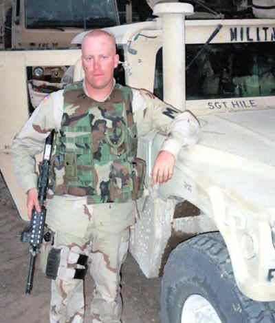 by: PHOTO COURTESTY OF MIKE HILE - Mike Hile is shown by his Jeep in Iraq. He has seen combat during his tour of the Middle Eastern nation.