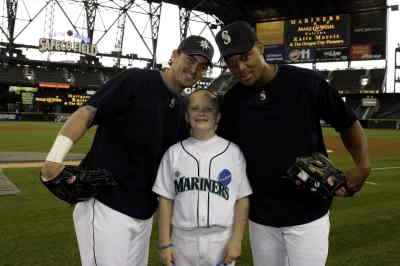 "by: Photos courtesy of Ben VanHouten - Katie Morris with Jeremy Reed, left, and Adrian Beltre, at Safeco Field with her name in lights in the background. Katie also had the opportunity to run the bases. Her special uniform says ""Morris"" and ""1"" on the back."