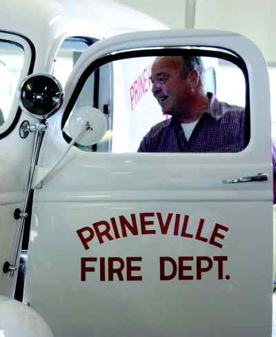 by: KATE WENNERSTROM/CENTRAL OREGONIAN - State Representative George Gilman looks over the recently restored 1946 GMC 3/4 ton ambulance.  Gilman was visiting Prineville to attend the town hall meeting.  The ambulance was purchased in 1947 from Wentworth and Erwin and used by Crook County Fire and Rescue (CCFR) until it was replaced in 1957 with a Cadillac ambulance.  It stood dormant for 10 to 15 years before the CCFR had it restored by Ricky B's Restorations of Prineville.