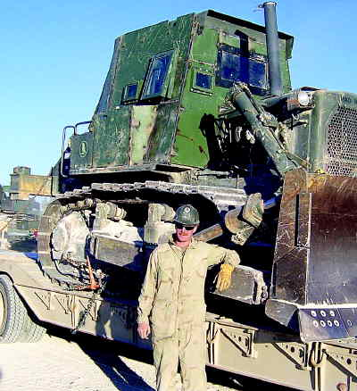by: CONTRIBUTED PHOTO - Robert Wolverton Jr. of Prineville stands before an armor plated dozer. The machine repairman first class was stationed in the Al Anbar province in Iraq for nine months.