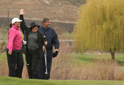 by: ANDREW MATHESON/CENTRAL OREGONIAN - Stephanie Whitcomb, middle, hits what would be the longest putt of the afternoon on Saturday at Meadow Lakes Golf Course. Whitcomb's putt was estimated to be between 35-40 feet, as she won the women's long putt prize at the Crook County benefit tourney. Megan Whitcomb, a former Cowgirl, and Brian Whitcomb, the president of the PGA, stand next to Stephanie all smiles.