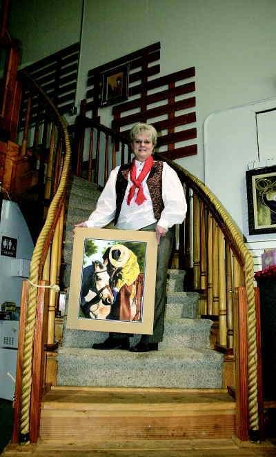 by: SHELBY CASE/CENTRAL OREGONIAN - Faye Taylor shows one of her award-winning paintings at the Bunkhouse Studio.