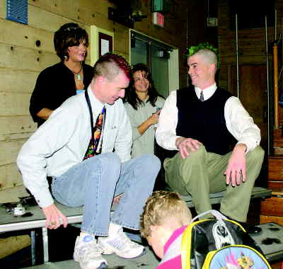 by: CENTRAL OREGONIAN - Cecil Sly Assistant Principal Jim Bates and school Counselor Darin Kessi get mohawk haircuts from hairstylists Robbie Hammon and Terri Hite.  Bates and Kessi told students they would go ahead with the haircuts if students reached a canned and dried food goal.