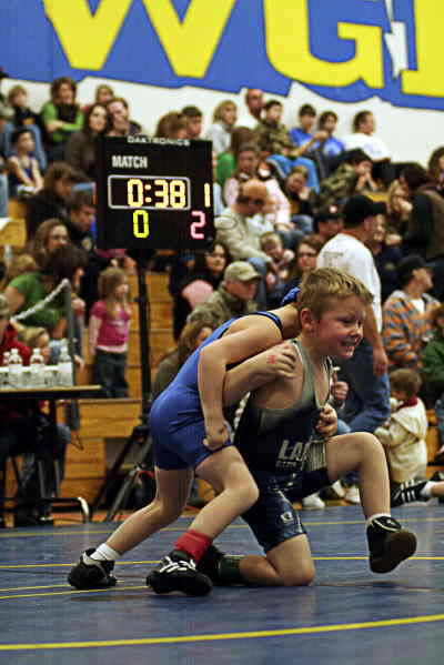 by: LON AUSTIN/CENTRAL OREGONIAN - Clay Wilkins of the Crook County Mat Club wrestles Logan Hank from LaPine at Saturday's youth wrestling tournament.  One of the new wrestling clocks is in the background.