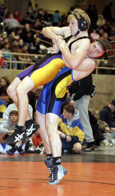by: LON AUSTIN/CENTRAL OREGONIAN - Dustin Champan picks up Hermiston's Ben Mallard during his 6-4 victory.