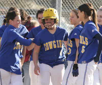 by: LON AUSTIN/CENTRAL OREGONIAN - Teammates congratulate Santana Reece, with helmet, after she hit her first of two homeruns on Tuesday in the Cowgirls 10-3 victory over Mountain View.  The win was the Cowgirls 10th win of the season, and makes them 1-0 to start league play.
