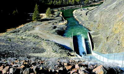 by: LON AUSTIN/CENTRAL OREGONIAN - Shown above: Water leaves the Prineville Reservoir on its way to irrigation canals.