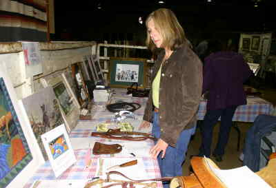 by: Shelby Case/CENTRAL OREGONIAN - Marianne Fellmer of Tumalo looks at some silent auction items at Sunday's Ochoco Western Arts Round-Up.