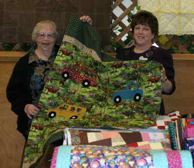 by: Kevin Gaboury/CENTRAL OREGONIAN - Quilters Jessie Strauch (left) and Cindy Prahl display one of the many quilts donated to local nonprofit agencies at the Prineville Senior Center on Wednesday.