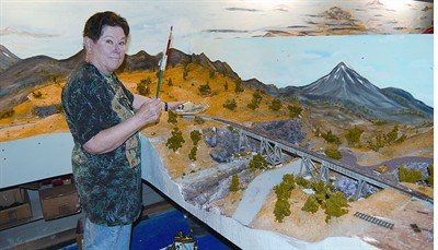 by: RAMONA MCCALLISTER/CENTRAL OREGONIAN - Alice Barr stands with brush in hand next to one of her recently completed backgrounds at the Ochoco Valley Railroad building. The building is located at the Crook County Fairgrounds, next to the Carey Foster Hall.