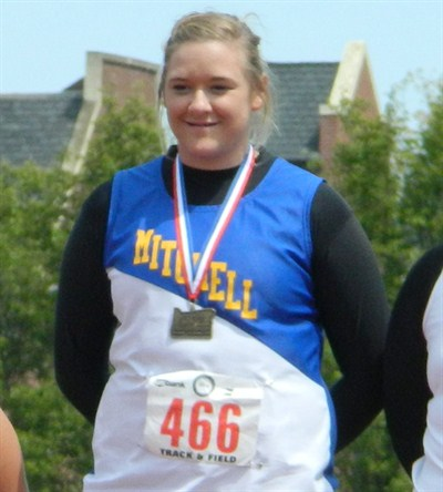 by: PHOTO COURTESY OF PAM WHITE - Megan White stands on the podium with one of her first-place medals from the state track and field championships. White won both the shot put and discus at the meet, which was held in Monmouth May 18-19.