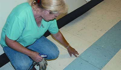 by: RAMONA MCCALLISTER/CENTRAL OREGONIAN - A janitor at Ochoco Elementary points out the issues with a portion of floor in the hallway