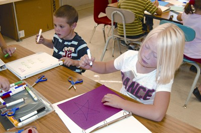 by: RAMONA MCCALLISTER/CENTRAL OREGONIAN - Casyn Jamasen and Lakyra Walker, kids in the After The Bell program, work on creating their science notebooks, which will be used to hold data throughout the year in science projects.