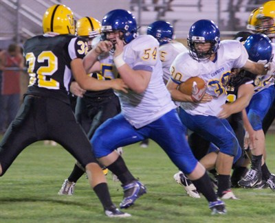 by: PHOTO COURTESY OF DOUG SMITH - Aaron Swindle runs the ball behind the block of Jason Williams. The Cowboys suffered their first loss of the season as they fell 31-12 to the Cascade Cougars Friday night.