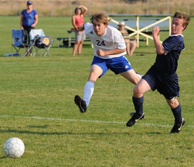 by: LON AUSTIN/CENTRAL OREGONIAN - Zane Abrams (24) drives the ball past a La Pine defender for Crook County's third goal of the match. The Cowboys went on to take a 14-2 victory while Abrams finished with four goals.