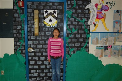 by: RAMONA MCCALLISTER/CENTRAL OREGONIAN - Natalie Orozco stands in front of Mrs. Fletcher's fifth grade classroom. In the background are decorations for King Arthur's Castle and the associated coat of arms. Each classroom has a similar theme outside of their door to accompany the storyline theme of medieval times.
