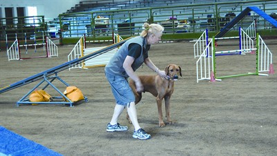 "by: RAMONA MCCALLISTER/CENTRAL OREGONIAN - Sandy Lachowski works with her Rhodesian Ridgeback, Magic, immediately before the dog begins the ""excellent"" dog agility trial at Saturday's competition."