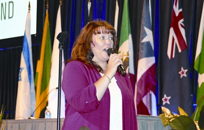 by: CONTRIBUTED PHOTO - Mary Chapman, a permit technician for the Crook County Building Department sang the National Anthem at the International Code Council.