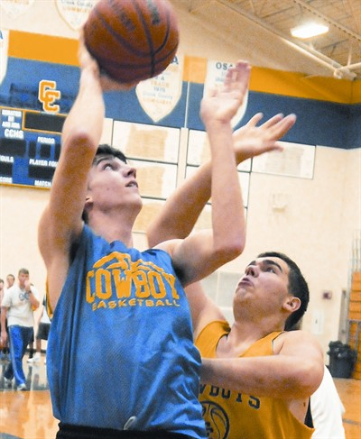 by: LON AUSTIN/CENTRAL OREGONIAN - Dillon Dean goes up for a shot against Michael Egbert during a recent practice. The Cowboys have a veteran team with 10 seniors as well as some underclassmen with varsity experience.