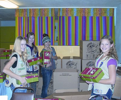 by: CONTRIBUTED PHOTO - Members of local Girl Scout Troop 50016 help organize the hundreds of Operation Christmas Child shoe boxes collected in Prineville. Pictured left to right are Emmalie McCoy, Megan Forbes, Vanessa Younger, and Alliya Day.