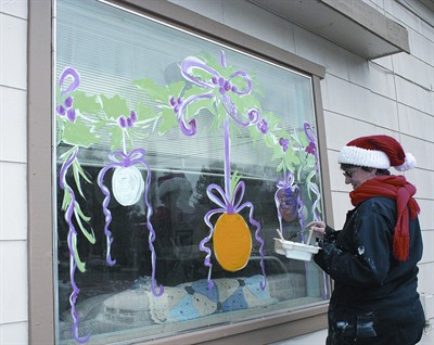 by: JASON CHANEY/CENTRAL OREGONIAN - Jean Christine paints a Christmas window display for the Rebel's Roost building in downtown Prineville.