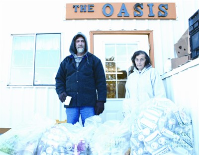 by: JASON CHANEY/CENTRAL OREGONIAN - Volunteers for The Oasis, Scott Green (left) and Ana Kramer, show several bags of cans that local residents have donated to the facility. Oasis manager Rich Will said the cans help pay the rent for their building.