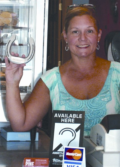 by: JASON CHANEY/CENTRAL OREGONIAN - Pine Theater co-owner Oniko Mehrabi holds up one of the horseshoes that they will continue to sell as a fundraiser for the purchase of digital movie projectors.