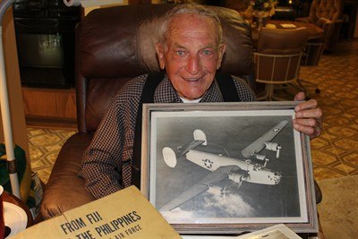 by: Photo by Susan Matheny - Ninety-one-year-old Bob Lundy holds a photo of the B-24D plane he flew on during the war.