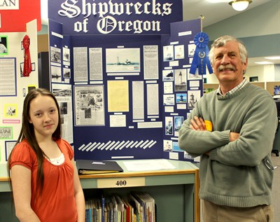 by: Photo By Joe McHaney - Jefferson County Middle School student Carly Breach, left, and Jerry Ramsey of the Jefferson County Historical Society stand next to Breach's first-place display about Shipwrecks of Oregon.