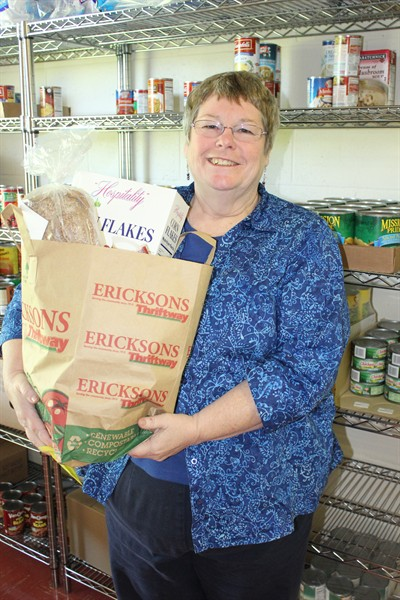 by: Photo by Susan Matheny - The Rev. Janet Farrell holds a bag of groceries given out through one of the United Methodist Church's six food ministries.