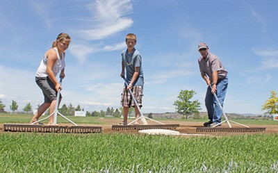 by: Photo By Joe McHaney - Brad Holliday, right, and his son Jared, middle, and daughter Hannah, left, spent time raking the Majors Little League baseball fields at Juniper Hills Park prior to the District 5 all-star tournament.