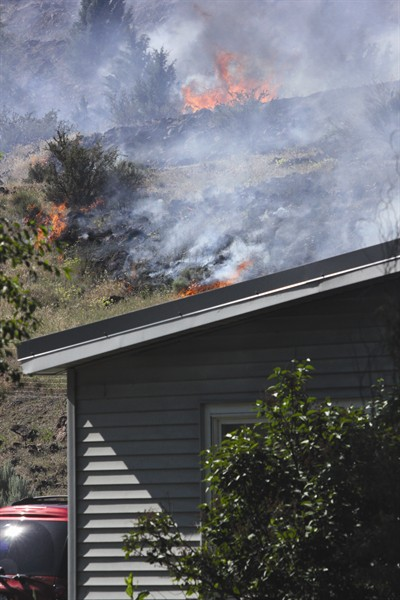 by: Photo by Joe McHaney - A fast moving fire threatened two homes and three other structures on the hills west of Madras on July 2.