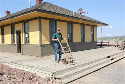 by: Photo by Susan Matheny - Metolius Public Works Supervisor Pat Hanenkrat stands on the deck of the repainted depot with an old keg dolly  that was found in the storeroom.
