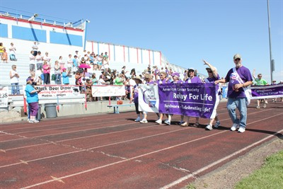 by: Photo by Susan Matheny - The crowd at last weekend's Relay For Life event cheers for cancer survivors carrying a banner as they kick off the annual fundraiser with the survivor's lap. The event took place July 14 and 15. See related photos on page 18 in newspaper.