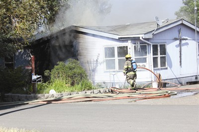 by: Photo by Joe McHaney - A firefighter works to put out the fire that caused extensive damage to a mobile home in Metolius on Sunday afternoon. The fire started in electrical wiring.