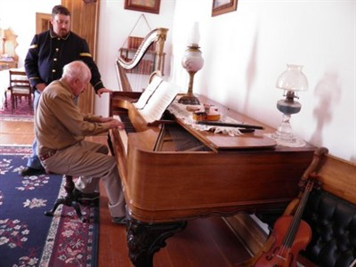 by: Submitted Photo - Mel Ashwill plays on Mrs. Custer's piano at the Custer Museum in North Dakota.