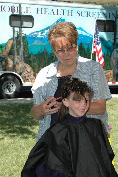 by: Photo by Susan Matheny - A girl gets her hair cut by a volunteer. One of the health checkup vans is visible in the background.