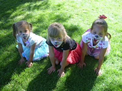 by: Submitted Photo - Face-painted puppies Cara Todd, Sienna Alvarado and Elise Todd play at the Summer Reading finale in the park.