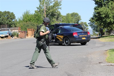by: Photo by Holly M. Gill - A member of the Central Oregon Emergency Response Team patrols the area around a home on Sixth Street in Metolius, where police believed they would find a man suspected in an armed robbery in Redmond. The man was arrested Monday in Portland.