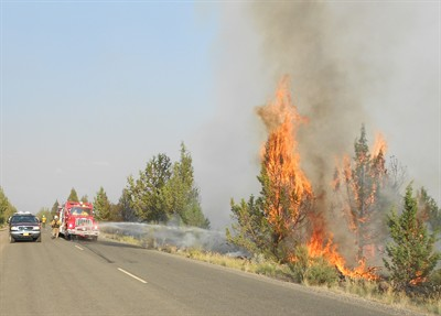 by: Photo by Jim Adkins - A fast-moving fire burns in sage and juniper just across from the Three Rivers subdivision on Monday. The fire was caused by Sunday night's lightning storm.