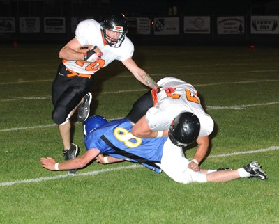 by: Photo By Joe McHaney - Tyler Warren, a 2008 Culver High School graduate, uses a block from Carlos Lee to slip past a Crook Cook County High School defender Aug. 11 in an alumni football game held in Prineville.