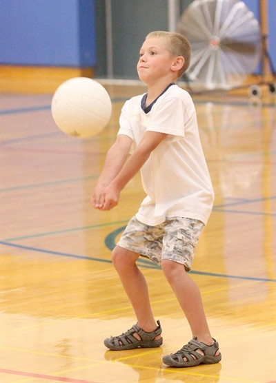 by: Photo By Joe McHaney - James Lange, 6, passes a volleyball during the Kids Club volleyball camp at Madras High School this week.