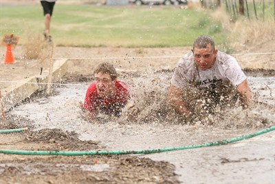 by: Photo by Joe McHaney - Culver High School opened the Crawdad Festival Aug. 18 by hosting the Redneck 5K Obstacle Course. Above, Brandon Hawes (left) and David Carnes (right) reach the end of the mud pit where runners were required to go below a two-foot rope. The mud pit was one of several obstacles that runners had to overcome throughout the 5K course.