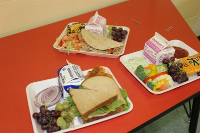 by: Photo by Susan Matheny - Examples of the new school lunch offerings with whole grain and more fruits and veggies.