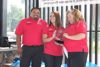 by: Submitted photo - BestCare Prevention Specialists Edgar Pineda, left, and Mandi Puckett, present a special surprise Award of Excellence to coworker Cindy Brockett, right, for her work teaching prevention programs in the schools.