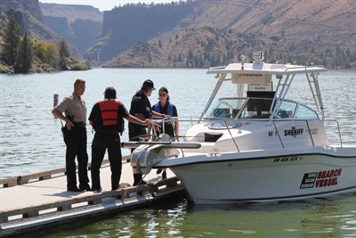 by: Photo by Holly M. Gill - Jefferson County Sheriff Jim Adkins, left, confers with a search team from Klamath County – Capt. Conrad Caillouette, Mike Parsons and Jani Arnold – on Friday, after the sonar equipment on the front of the 23-foot search vessel was damaged by an underwater cable in the slalom ski course at Lake Billy Chinook. The equipment damaged by the cable was repaired, and the team resumed their search on Saturday,  using sonar to map the area of the lake where Gene Harris, 73, of Madras, was believed to have gone into the water on Thursday to rescue his son Mark Harris, 37. Both died in the incident, but Mark Harris' body was recovered at the scene, while Gene Harris' body had not yet been located by Tuesday afternoon.