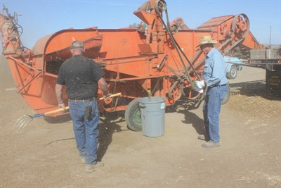 by: Photo by Susan Matheny - Jim Hanson, left and Walt Zistel check on the threshing machine's production as chaff and dust fly everywhere.